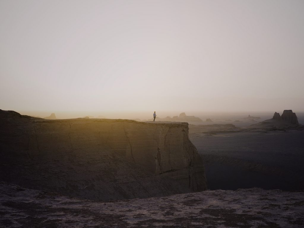 A man stands on the yardangs in the Lut Desert